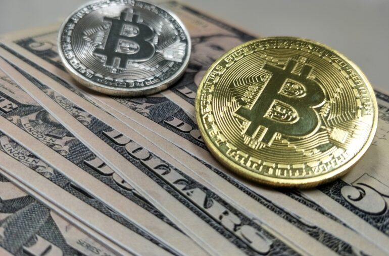 Picture of two bitcoins laying on top a stack of dollar bills